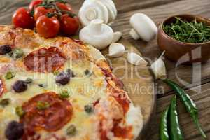 Various species with pizza and tomato on a wooden tray