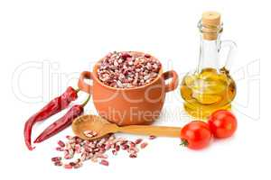 beans in a ceramic pot, cooking oil and vegetables isolated on w