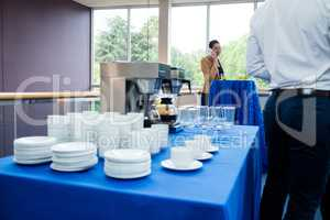 Coffee maker with coffee cup and glass on table