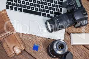 Close-up of digital camera, lens, memory card, laptop on table