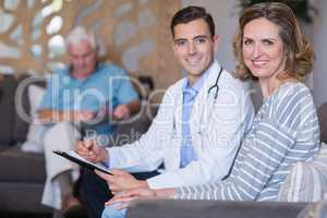 Portrait of doctor and woman sitting on sofa with medical report