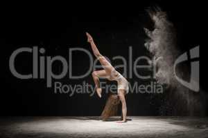 Graceful blonde dancing in white dust studio shot