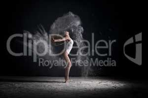 Slender blonde dancing in white dust studio shot