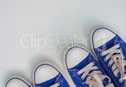 two pair blue neakers youth on a white wooden surface