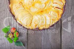 Apple pie with custard on wooden table