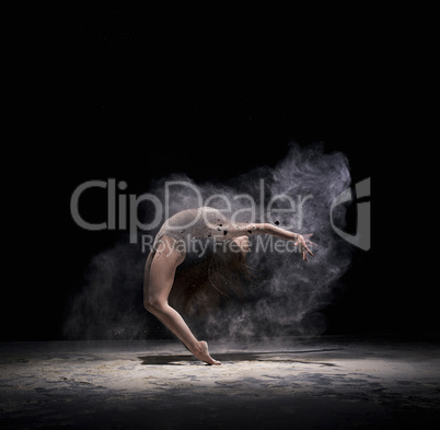 Graceful woman dancing in cloud of white dust