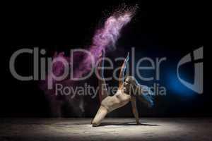 Slender blonde posing in color powder cloud