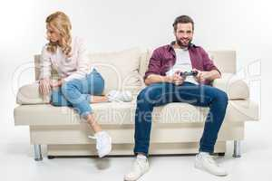 Offended woman and man playing with joystick
