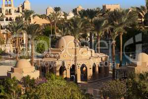 An oasis of palm trees and greenery photo. Houses along the beach in Makadi, Egypt