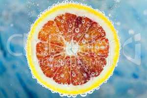 Blood orange slice falling into water