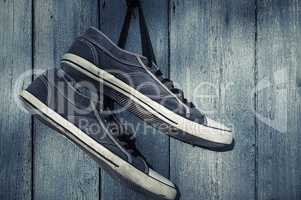 Blue textile torn sneakers hanging from a nail