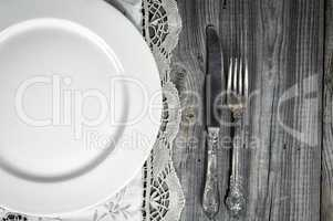 White empty plate on the tablecloth with lace, near knife and fo