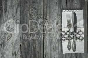 Cutlery knife and fork on gray wooden surface