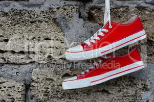 Youth red sneakers with laces hanging on a brick wall background