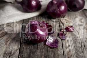 Red onions in the husk on the gray old wooden surface