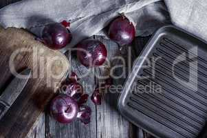 black frying pan and a red onion on a gray wooden surface