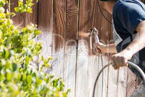 Professional Painter Spraying Yard Fence with Stain