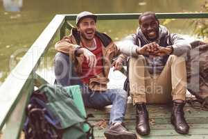 Young men with backpacks sitting on pier