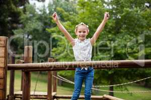 Girl standing with arms up on a playground ride in park