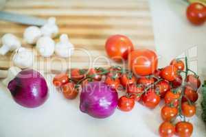 Cherry tomatos, onions and mushrooms on kitchen worktop