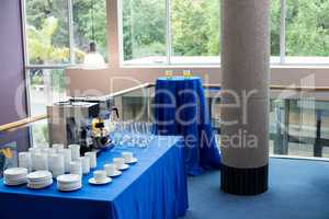 Coffee maker with coffee cup at glass on table