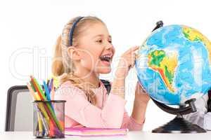 Happy schoolgirl exploring globe