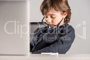 schoolchild in business suit sleeping near laptop