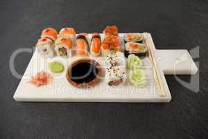 Assorted sushi set served with soy sauce and chopsticks on white board