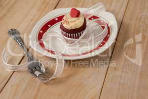 Plate with delicious cupcake decorated with a ribbon and fork