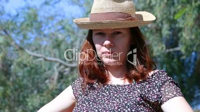 Young beautiful woman with red hairs and a straw hat sitting outside looking at the camera and then looking up seriously