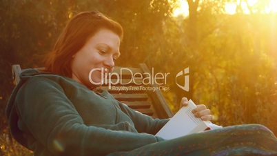 Young beautiful smiling woman with beauty patch on her cheek relaxs on a deck-chair reading a book in sunset back light