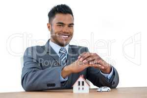 Smiling businessman protecting house model and car with hands