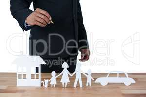 Mid section of businessman with paper cut out family, house and car at desk