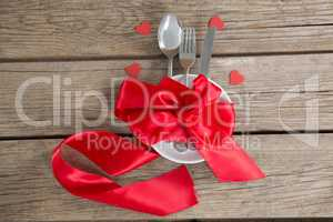 Cutlery and white plate tied up with red ribbon