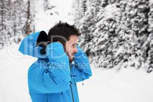 Skier wearing hooded jacket on snowy mountains