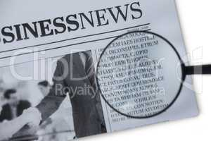 Magnifying glass on newspaper paper