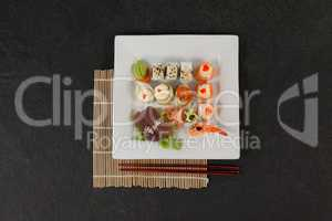 Assorted sushi set served with chopsticks in white plate on sushi mat