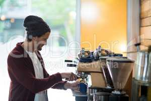 Owner making cup of coffee in espresso machine