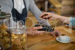 Woman paying bill through smartphone using NFC technology