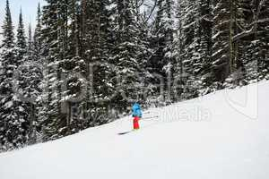 Skier skiing on snow covered mountain slope