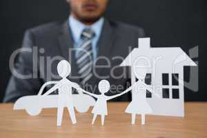 Paper cut out family chain with car and house at desk