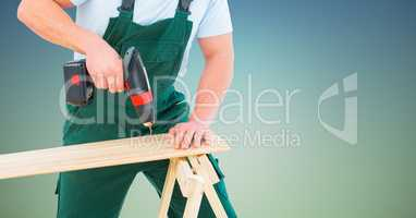 Composite image of Carpenter drilling against blue green background