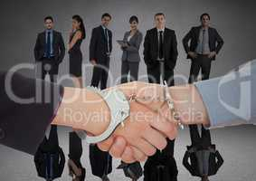 Handshake with handcuffs in front of business people in grey room