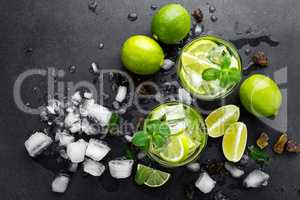 Summer mint lime refreshing cocktail mojito with rum and ice in glass on black background top view