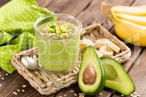 Avocado and banana smoothie with oats with ingredients in glass jar on wooden background, healthy eating