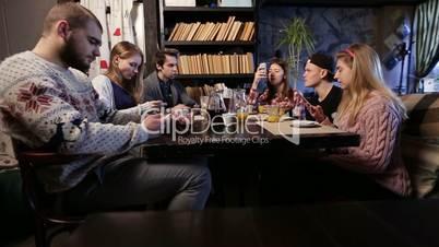 Gen z. Young friends using smart phones in cafe.