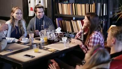 Happy teenagers spending leisure in cafe