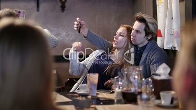Hipster couple doing selfie with cellphone in cafe