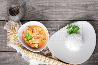 Chicken curry and rice served on a wooden surface.