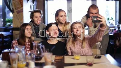 Happy hipsters doing selfie with cellphone in cafe